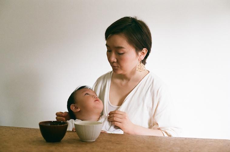 【写真】赤ちゃんを抱いて優しく見つめているたむらまなさん
