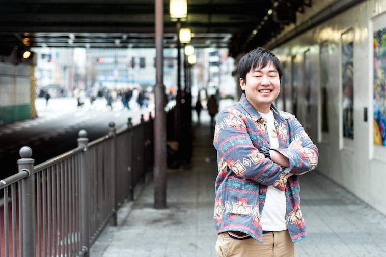 【写真】街頭で笑顔で立っているむまつらひでのぶさん