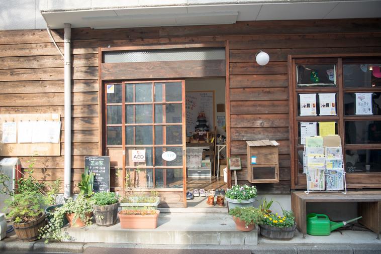 【写真】木でできた建物の玄関前には植物が植えられたプランターが並ぶ