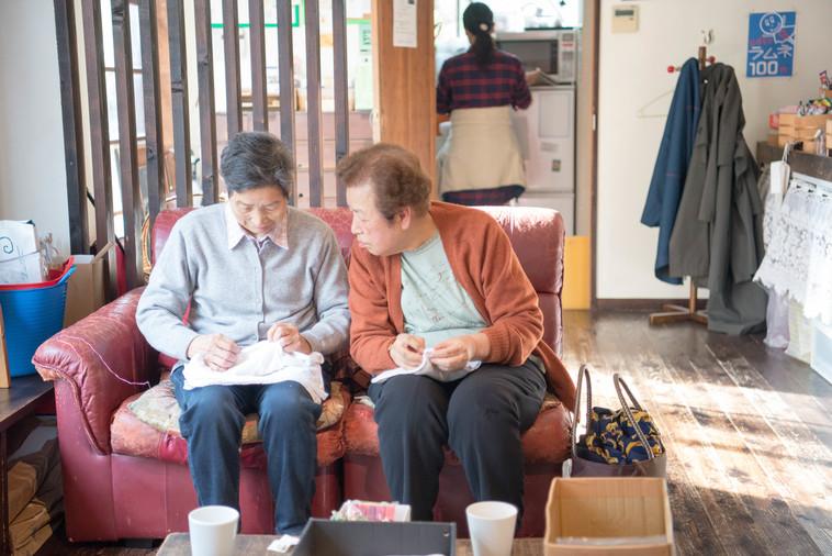 【写真】ソファに座ったおばあちゃん2人が、雑巾を縫っている