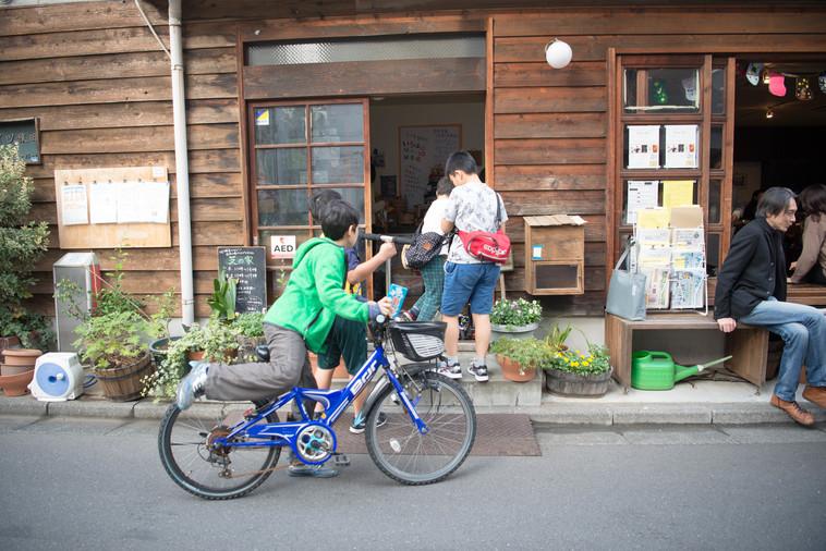 【写真】自転車にのって男の子が芝の家にやってきたところ。友人と待ち合わせをしているよう
