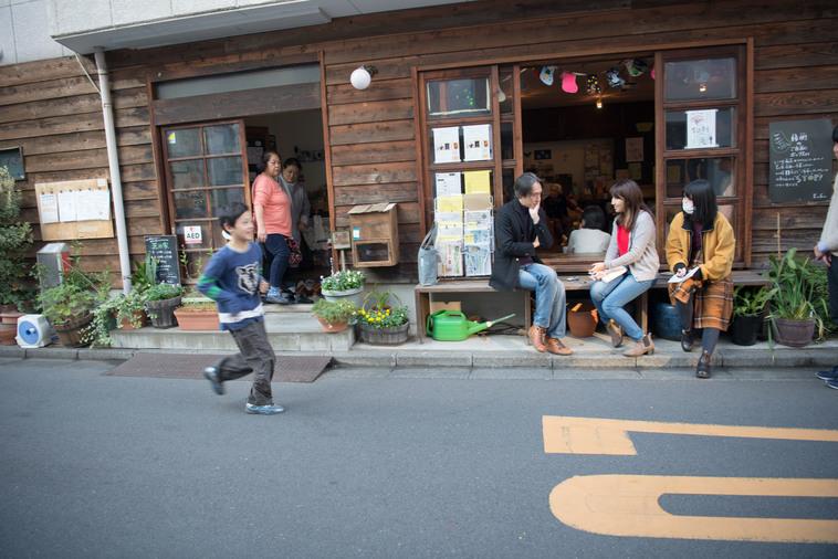 【写真】縁側に座ってインタビューをしている。近くでは子どもたちが走り回って遊んでいる