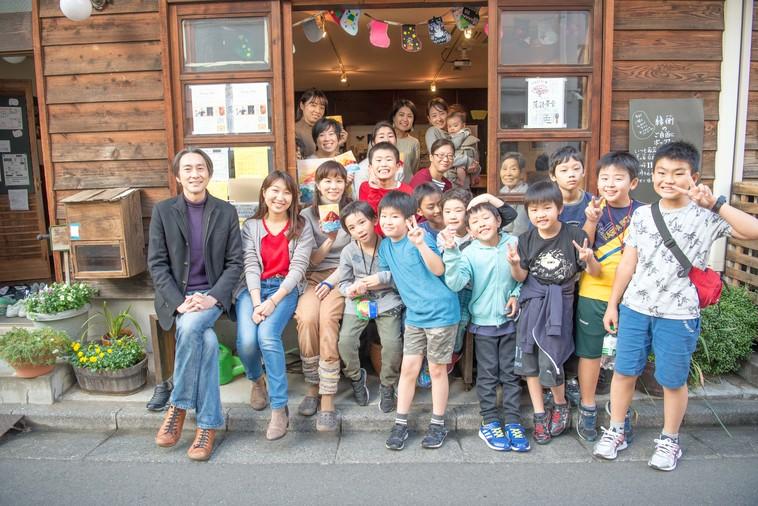 【写真】縁側にたくさんの子どもや大人が混ざって並び、カメラに向かって笑顔を向けている
