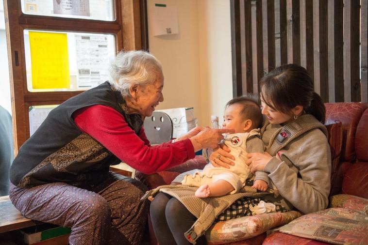【写真】おばあちゃんがお母さんの膝に座っている赤ちゃんのほっぺを笑顔でつついている