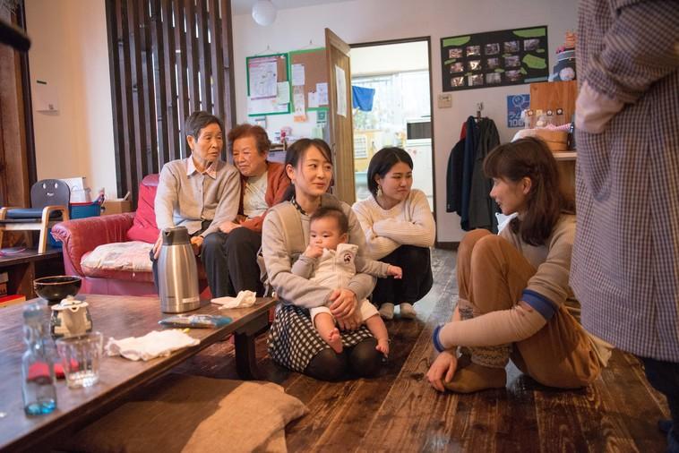 【写真】ソファに座って話をするおばあちゃん。近くには赤ちゃんを抱っこするお母さんと話をするかとうりょうこさんが