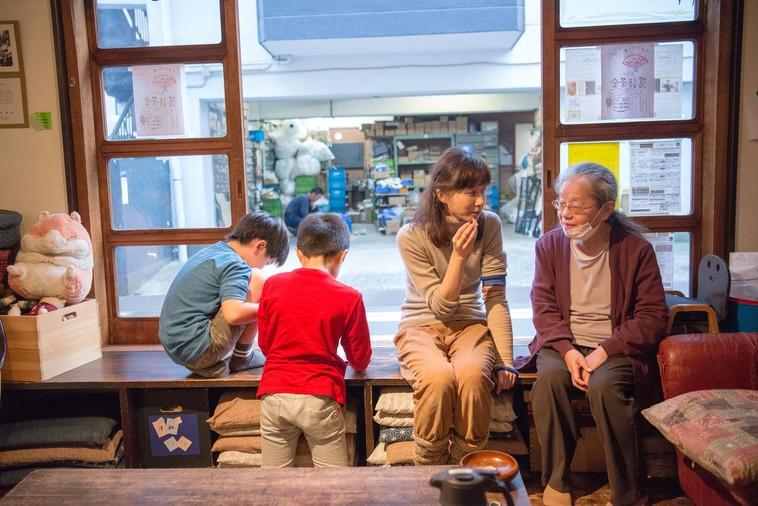 【写真】縁側に座っておばあちゃんと話をするかとうりょうこさん。その横では子どもたちがゲームをしていて、近くにいるけれど別々のことをしている、ということが自然に成り立っているのが感じられる