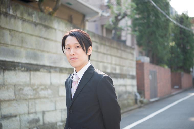 【写真】住宅街をスーツ姿で立つすずきしんぺいさん