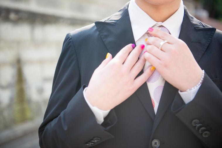 【写真】すずきしんぺいさんのスーツ姿。丸の模様が入ったネクタイをつけている。
