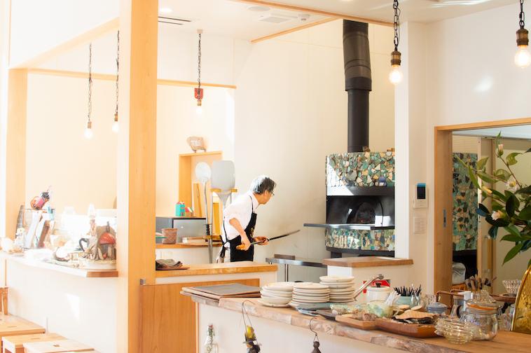 【写真】スタッフがらんどねのキッチンにある釜でピザを焼いている