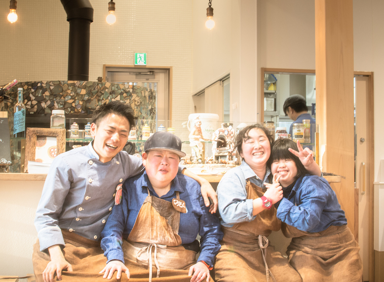 【写真】明るい雰囲気の店内で、肩を組みながら笑顔を向けるらんどねのスタッフ4人
