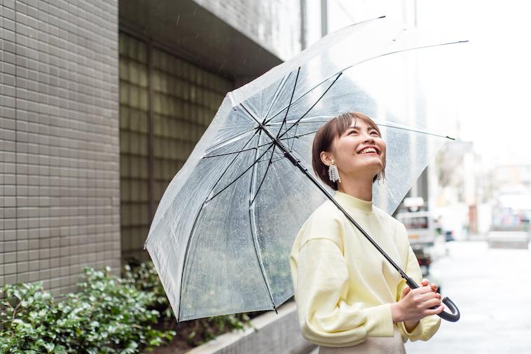 【写真】傘をさして空を笑顔で見上げているたなかれいかさん