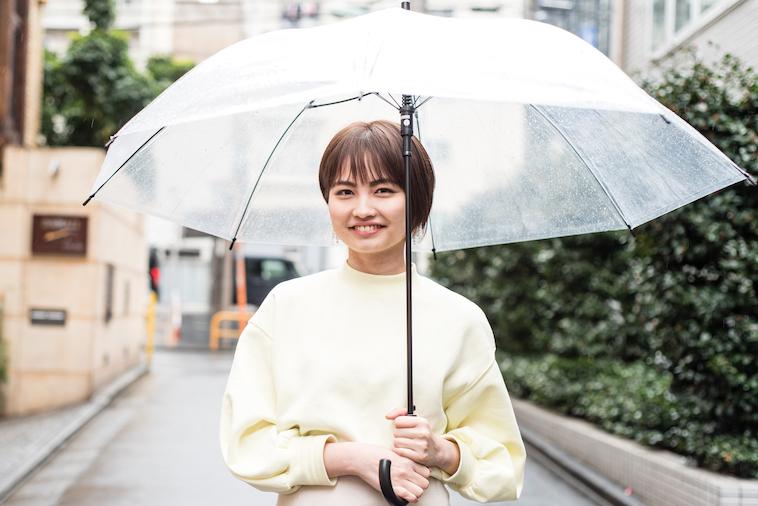 【写真】傘をさして微笑んで立っているたなかれいかさん