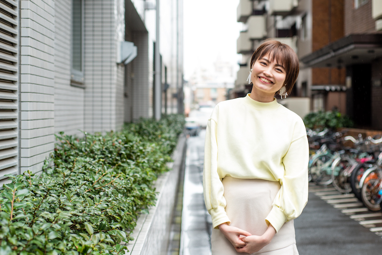 【写真】住宅街の道で笑顔で立っているたなかれいかさん