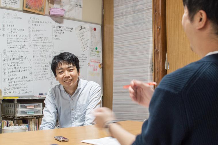 【写真】インタビューに応えるむかいやちのりあきさん。笑みを浮かべている。