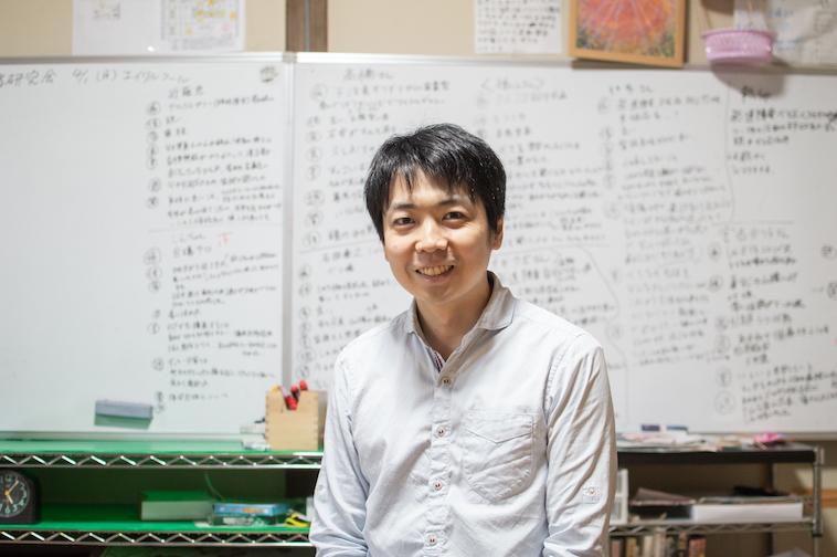 【写真】べてぶくろを立ち上げたむかいやちのりあきさん。当事者研究で使用された文字ぎっしりのホワイトボードの前で笑みを浮かべている。