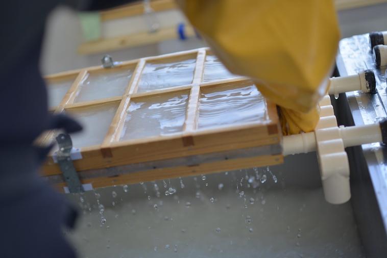 【写真】大きな機材を使って紙漉きをする