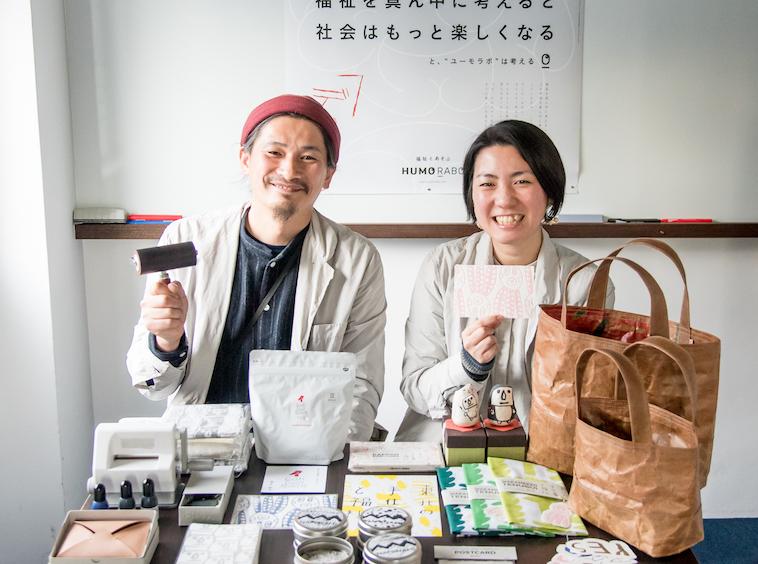 【写真】バッグや手ぬぐい、ポストカードなどデザイン制作した商品を並べた机を前に微笑むHUMORABOまえかわゆういちさんとまえかわあきこさん