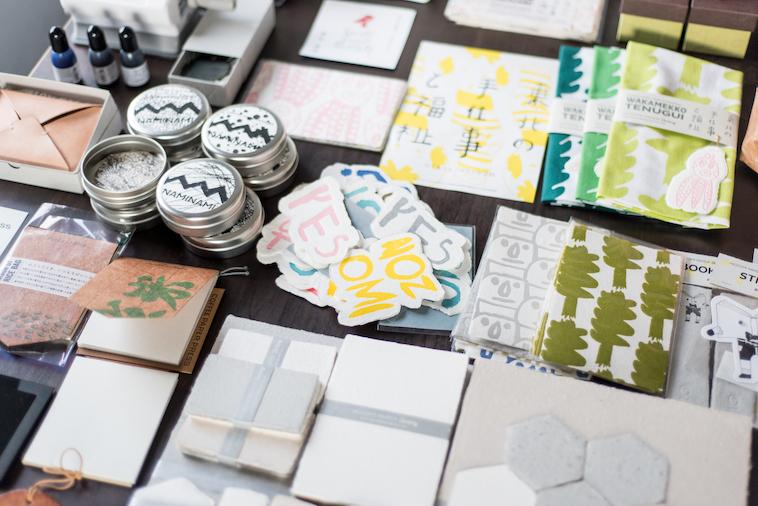 【写真】手づくりのプロダクトであるステッカー、メモ帳、手ぬぐいが机の上に所狭しと並べられている