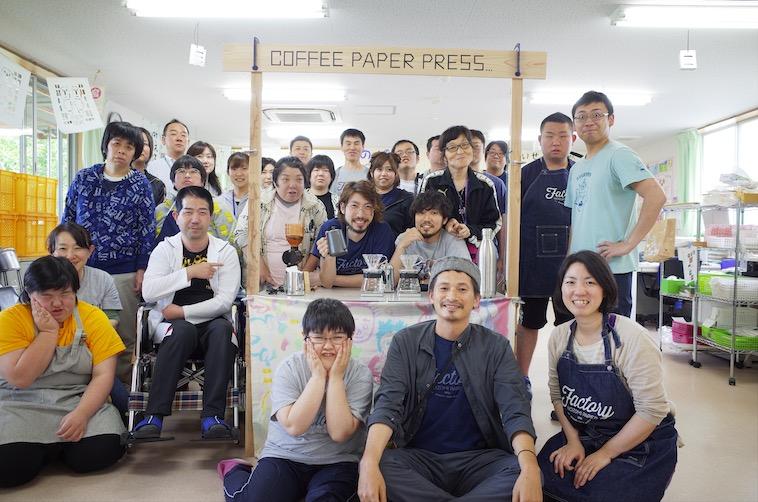 【写真】のぞみ福祉作業所のみなさんと、COFFE PAPER PRESSの簡易屋台の前で集合写真を撮るまえかわさん夫妻