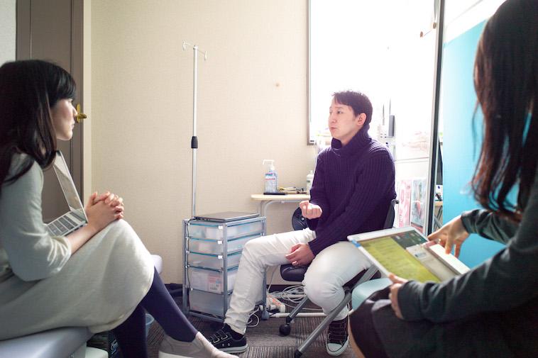 【写真】診察室でインタビューに答えるすずきゆうすけ先生と、真剣な表情でインタビューをするライターのむかいはるかさん