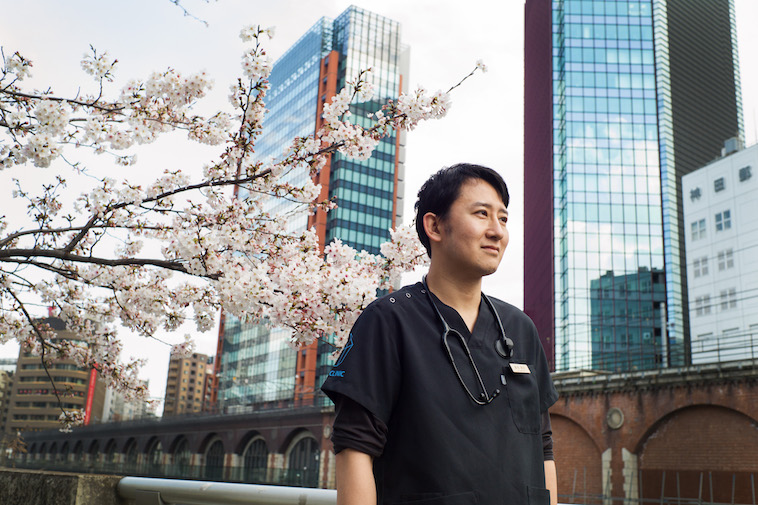 【写真】街頭の桜の木の前に立ち、どこかをみつめるすずきゆうすけ先生