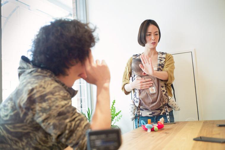 【写真】みくちゃんを抱きながら真剣な表情でインタビューに答えるまみさんとそれを見守るはじめさん