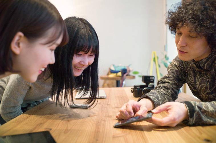 【写真】さくくんの当時の様子の写真をスマートフォンで見せるかとうはじめさんと笑顔でみるライターのおかもとみきさんと編集部のまつもとあやか