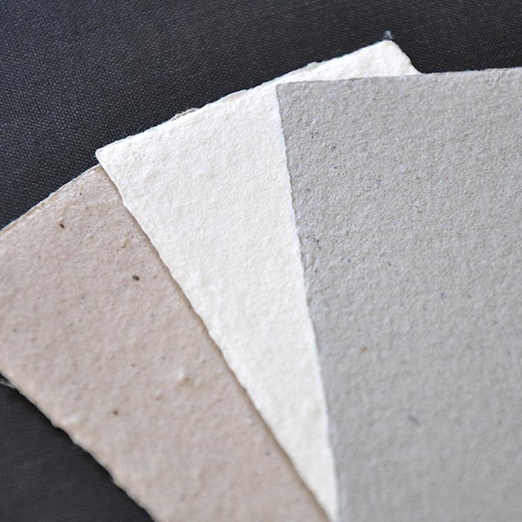 【写真】NOZOMI PAPERはコーヒーの出がらしで染めたもの、牛乳パック100パーセントのもの、古新聞100パーセントのものそれぞれ風合いが異なる