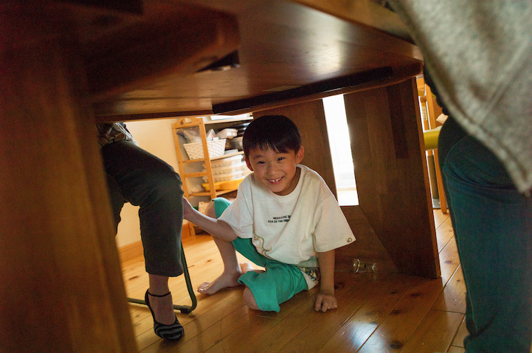 【写真】リビングのテーブルの下に隠れて、遊んでいる小学生。とても楽しそうだ。