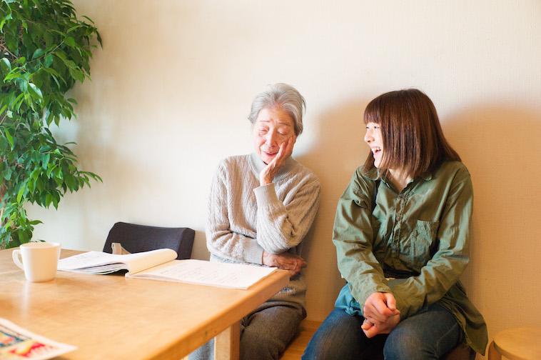 【写真】リビングの椅子に隣り合って座る利用者とスタッフ。笑みを浮かべている。