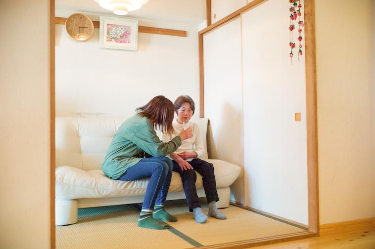 【写真】畳の部屋にソファに座り、お水を飲んでいる利用者とそれを見守るスタッフ。