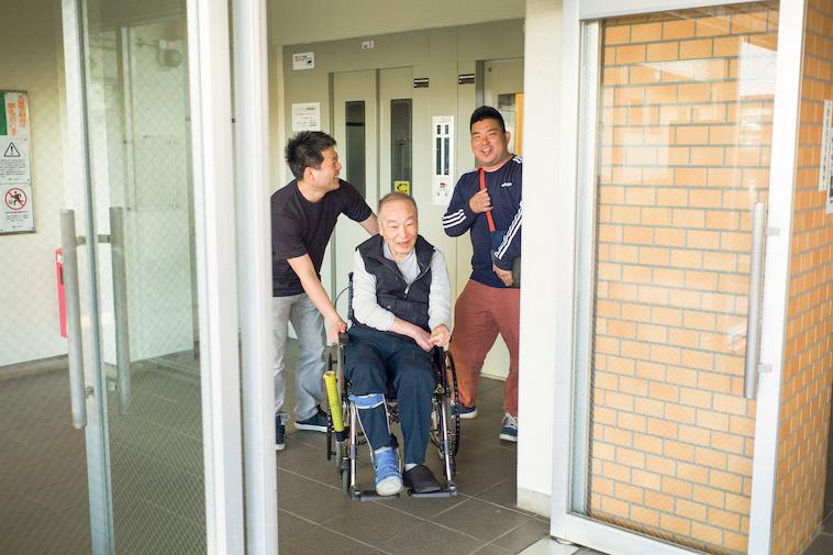 【写真】団地内にあるエレベーターの前で、車椅子に乗る利用者と会話しながら歩くスタッフ。楽しそうだ。