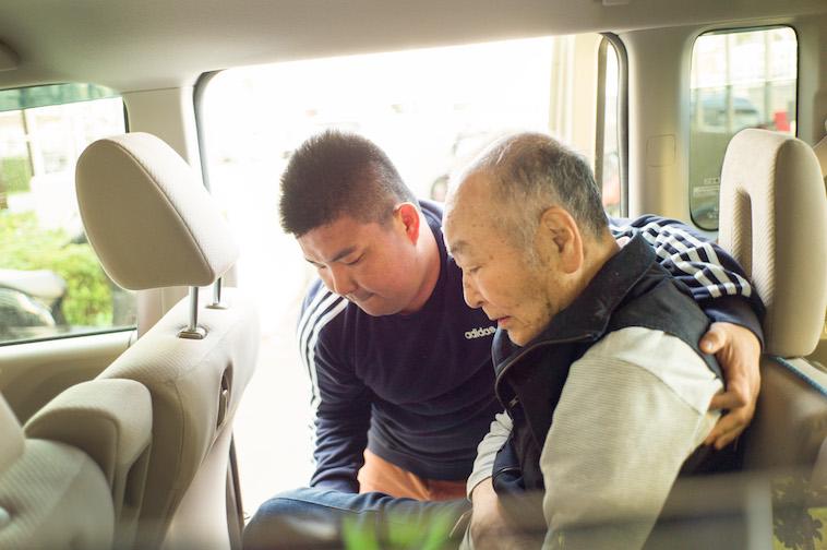 【写真】車に乗るために、利用者をサポートするスタッフ。お互い体を任せあっている。