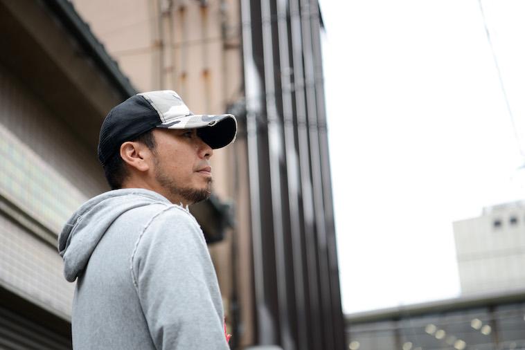 【写真】帽子を深く被り遠くを見つめるすずきだいすけさん