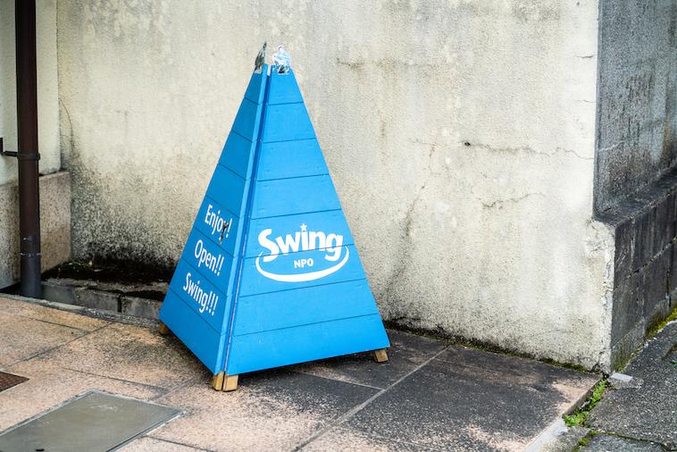 【写真】スウィングと書かれた看板が建物前に置かれている