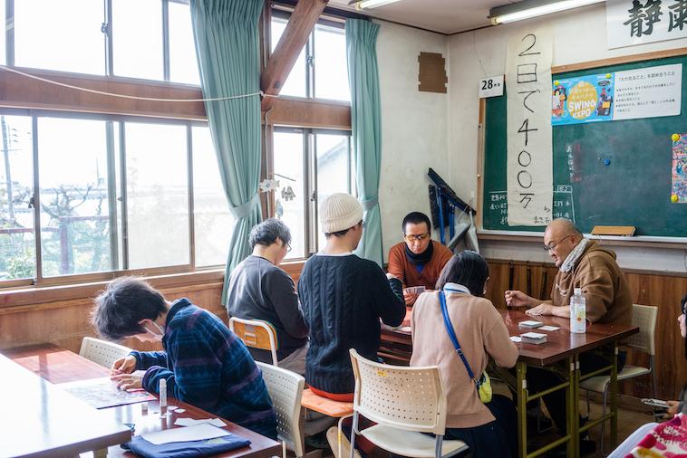 【写真】机を囲んでポーカーで遊んでいる利用者たち。そのすぐ近くでは一人で作業をする人もいて、それぞれが自由に過ごしている