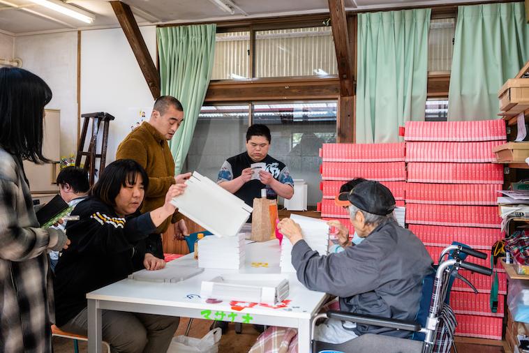 【写真】メンバーが八橋の箱おり作業をしている。立っていたり座っていたり、車椅子に座っていたりと自由