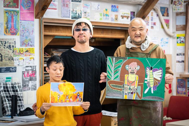 【写真】スウィング代表の木ノ戸さんと、自分の作品を持って並ぶメンバー2人