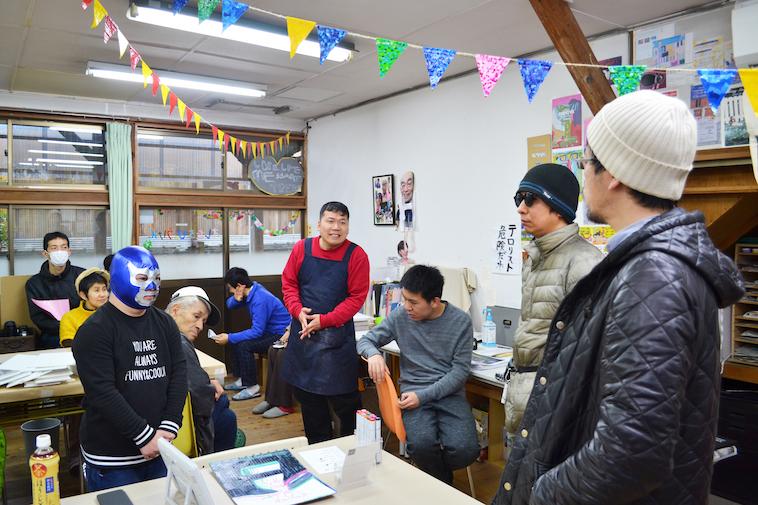 【写真】朝礼でメンバーが話をしている様子。プロレスで使われるようなマスクをかぶっているメンバーや、何か別の作業をしているメンバーもいる