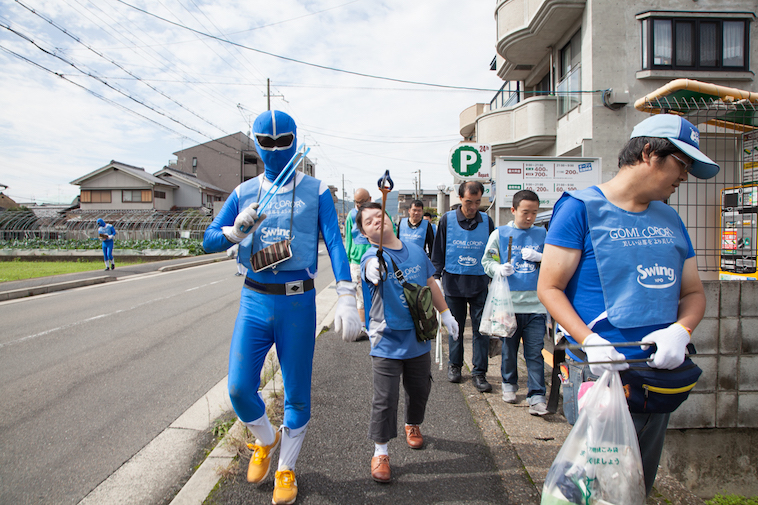 【写真】道路で清掃活動の「ゴミコロリ」を行なっている様子。青いTシャツや、青い戦隊レンジャーの衣装を着ている