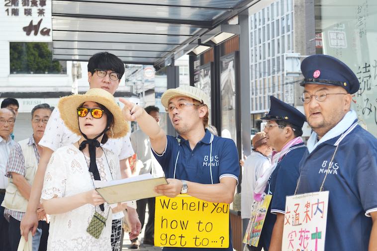 【写真】京都人力交通案内「アナタの行き先、教えます。」の様子。スウィングの利用者が道ゆく人に案内をしている