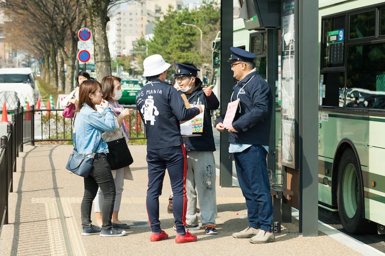 【写真】バス停で交通案内をするメンバーのQさんとXLさん。駅員のような帽子をかぶっている