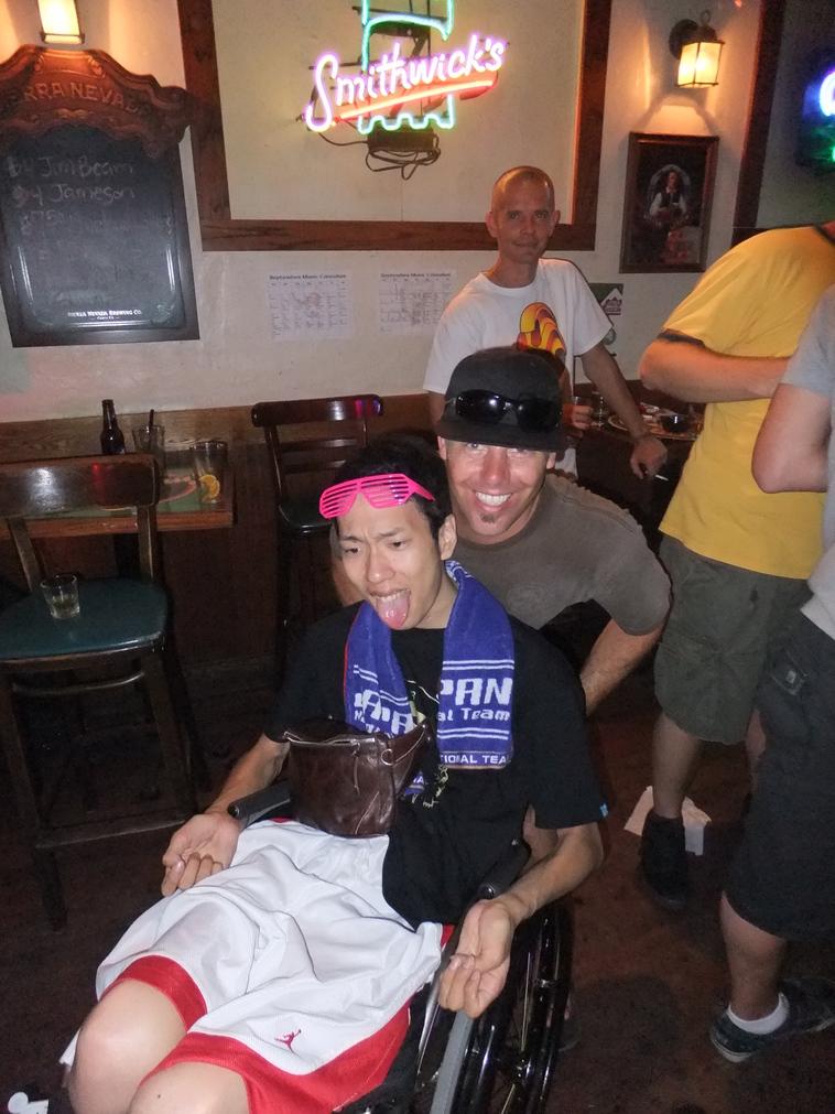 【写真】ハワイの方が、みよさんの車椅子を笑顔でおしている。みよさんは舌を出して楽しそうな様子。