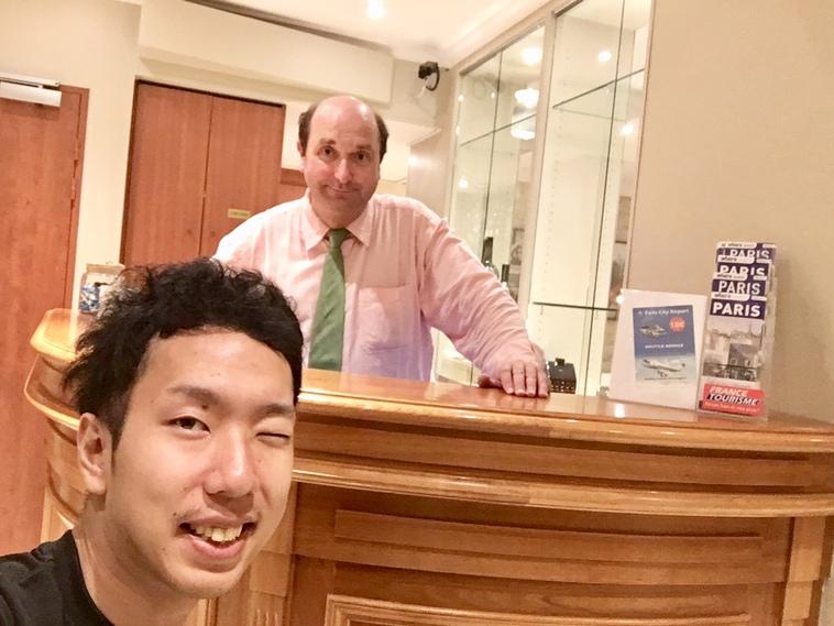 【写真】ホテルのフロントで笑顔をみせるピエールと、ウインクをするみよさん