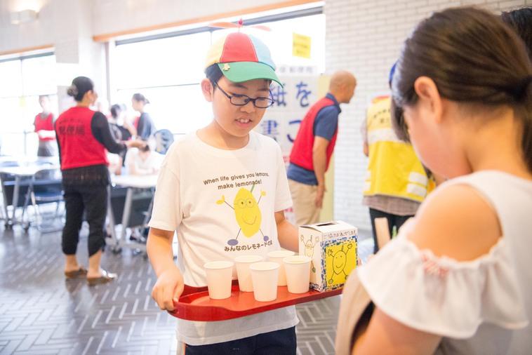 【写真】しろうさんがお盆を持ってレモネードを販売している様子
