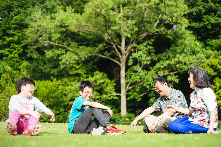 【写真】芝生に座り楽しそうに話すご家族