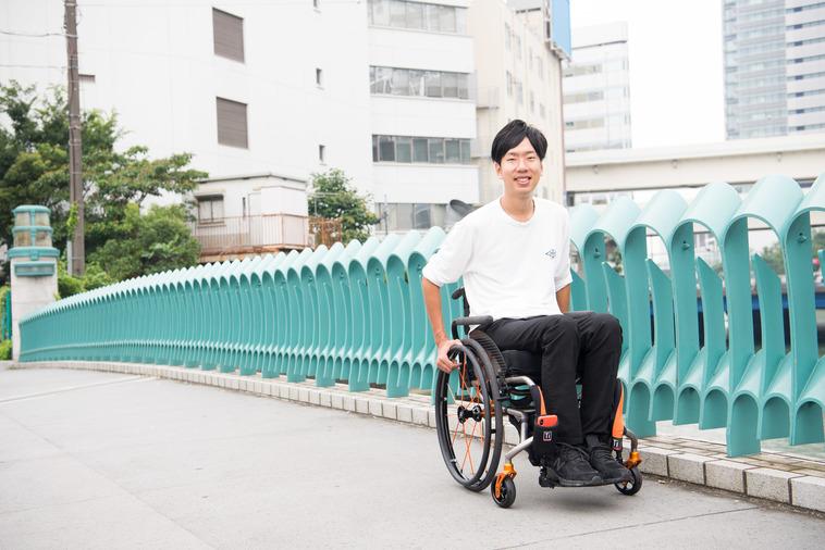 【写真】街頭で車椅子に座り笑顔をみせるみよたつやさん