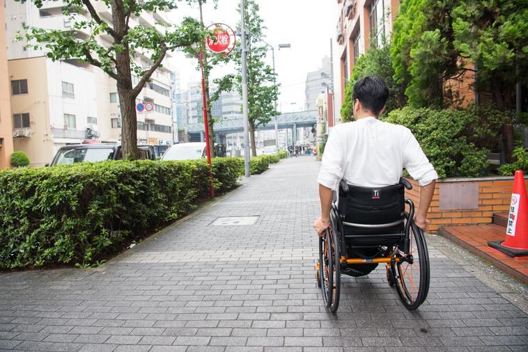 【写真】街頭を、車椅子を押して移動するみよさんの後ろ姿