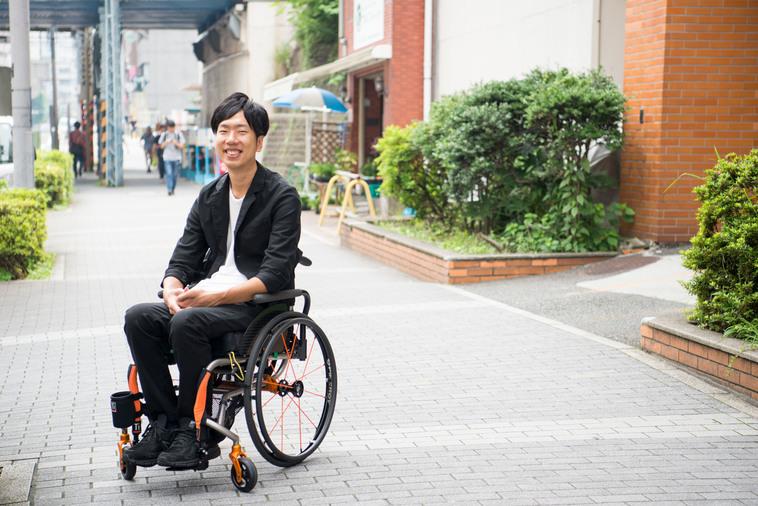 【写真】街頭で車椅子に座り満面の笑みをみせるみよたつやさん