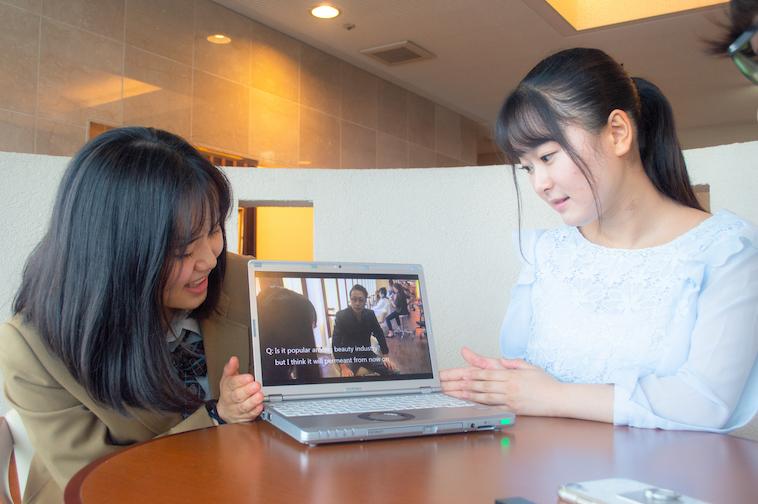 【写真】まりあさんとゆりあさんがパソコンをみせている。パソコンには、ウィッグを患者さんに提供している時の動画がうつされている。